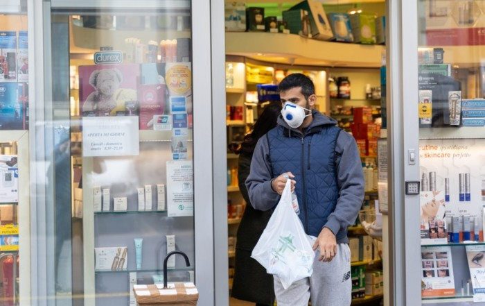 A man in face mask coming out of a pharmacy shop