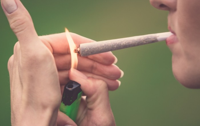 Woman lighting up marijuana joint