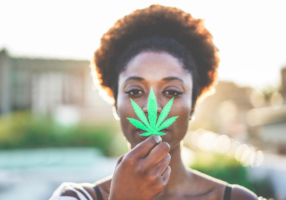 Young black girl holding marijuana leaf
